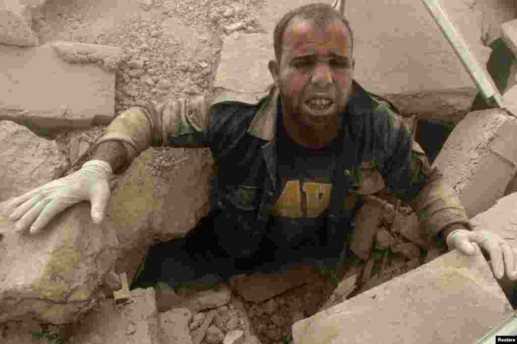 A civil defense member is stuck under debris at a site hit by what activists said were two barrel bombs dropped by forces loyal to Syria's President Bashar al-Assad in the Al-Shaar neighborhood of Aleppo.