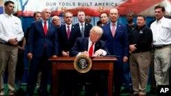 El Presidente Donald Trump firma una orden ejecutiva sobre el establecimiento de la Oficina de Políticas de Comercio y Manufactura. Lo hizo junto con el vicepresidente Mike Pence; el secretario de Asuntos de Veteranos, David Shulkin; y el secretario de Comercio de Estados Unidos, Wilbur Ross. Harrisburg, Pensilvania, sábado 29 de abril de 2017.