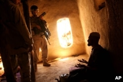 FILE - A U.S. Army soldier and an Afghan translator interrogate a person in the Bagh village of Khakeran Valley, Zabul province, Afghanistan, June 2005. Americans are for the first time targeted by the ICC for possible abuses in Afghanistan.