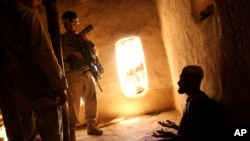 FILE - U.S. Army soldier and an Afghan translator interrogate person in the Bagh village of Khakeran Valley, Zabul province, Afghanistan, June 2005.