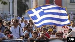 Tài xế taxi vẫy cờ Hy Lạp trước mặt cảnh sát chống bạo động trong 1 cuộc biểu tình ở Thessaloniki, thứ Bảy, 10/9/2011