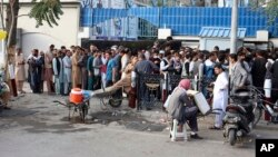 Afghans wait in long lines for hours to try to withdraw money, in front of Bank in Kabul, Afghanistan, Monday, Aug. 30, 2021. The Taliban have limited weekly withdrawals to $200. (AP Photo/Khwaja Tawfiq Sediqi)