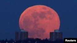 A full moon rises behind blocks of flats in north London, Britain, Jan. 31, 2018.