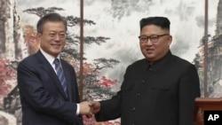 Prezidan Kore di Sid la, Moon Jae-In (agoch) ak lidè Kore di Nò a, Kim Jong Un (adwat) ki te bay lanmen nan fen 2èm jounen yon somè 3 jou nan Pyongyang, kapital Kore di Nò.