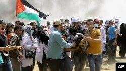 បាតុករប៉ាឡេស្ទីននាំយុវជនម្នាក់ដែលរបួសចេញពីកន្លែងបាតុកម្មនៅក្បែររបងព្រំដែនអ៊ីស្រាអែល នៅក្នុងតំបន់ Gaza Strip កាលពីថ្ងៃទី១៤ ខែឧសភា ឆ្នាំ២០១៨។