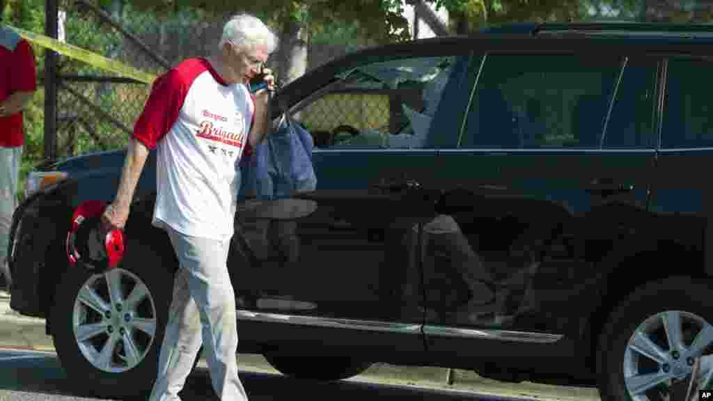 L'élu Jack Bergman, parle au téléphone en passant devant une voiture endommagé après des tirs, le 14 juin 2017, à Alexandria.