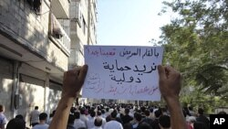 "People protest against Syria's President Bashar al-Assad on the first day of Eid Al-Fitr in the city of Suqba August 30, 2011. The banner reads: ""Need international intervention to protect us from Bashar's gangs"", August 30, 2011."