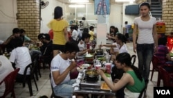 Transgender waitresses walk past customers dining on seafood hotpot at Thuy Linh, a restaurant famous for embracing the LGBT crowd, in Ho Chi Minh City, Vietnam, Apr. 2, 2013.