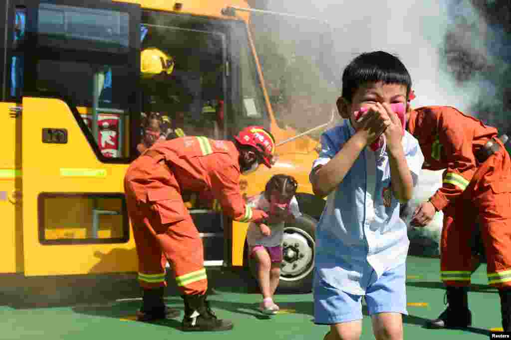 Firefighters instruct children evacuating a school bus during a fire drill at a kindergarten in Cangzhou, Hebei province, China, Aug. 27, 2018.