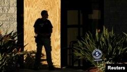 Agent Američke agencije za imagraciju i carine (ICE) čuva industrijsku zgradu na granici sa maksikom (Foto: Reuters/Mike Blake)