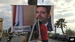"Workers hang a poster of Prime Minister Saad Hariri with Arabic words that read ""We are all Saad,"" on a seaside street in Beirut, Lebanon, Nov. 9, 2017."