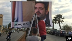 "Workers hang a poster of outgoing Prime Minister Saad al-Hariri with Arabic words that read ""We are all Saad,"" on a seaside street in Beirut, Lebanon, Nov. 9, 2017. Hezbollah has called on Saudi Arabia to stay out of Lebanese affairs, saying the resignation of Hariri ""has raised many questions."""