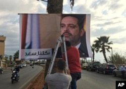 "Workers hang a poster of outgoing Prime Minister Saad Hariri with Arabic words that read ""We are all Saad,"" on a seaside street in Beirut, Lebanon, Nov. 9, 2017."