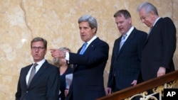 U.S. Secretary of State John Kerry, gestures in centre, with German Foreign Minister Guido Westerwelle, left Canadian Foreign Minister John Baird and Italian PM Mario Monti as theywalk down the stairs for a press conference on sexual violence against women during a G8 Foreign Ministers in London, April, 11, 2013.