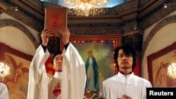 北京天主教堂裡的一名神職人員在做聖誕彌撒時高舉中文版的聖經。(2007年12月24日)