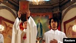 資料照: 北京天主教堂裡的一名神職人員在做聖誕彌撒時高舉中文版的聖經。 (2007年12月24日)