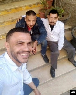 This photo taken in March 2020 provided by Egyptian coffee shop worker Hany Hassan, shows the father of four Hany Hassan, at right, and his friends taking a 'selfie' outside the coffee shop where he works, in Cairo, Egypt. (Courtesy of Hany Hassan via AP)