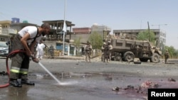 A fireman clears blood and debris as NATO soldiers stand at the site of an attack in Helmand province, Afghanistan, August 28, 2013.