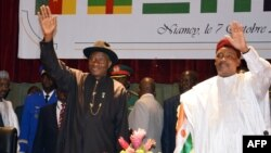 Nigeria's President Goodluck Jonathan (L) and Niger's President Mahamadou Issoufou wave while taking part in a regional summit focused on the fight against Nigerian Islamist extremist group Boko Haram, Oct. 7, 2014 in Niamey.