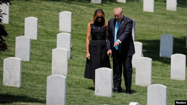"""El presidente de los Estados Unidos, Donald Trump, y la primera dama, Melania Trump, se agarran de las manos entre las lápidas mientras participan en el evento anual """"Flags-In"""" en el Cementerio Nacional de Arlington. Photo: Reuters."""
