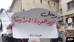 """Damashqda hukumatga qarshi namoyishga chiqqan mana bu qiz qo'lidagi plakatda shunday deyiladi: """"Ket, biz o'qishga qaytishni xohlaymiz""""."""