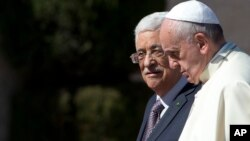 FILE - Pope Francis is welcomed by Palestinian President Mahmoud Abbas upon his arrival to the West Bank city of Bethlehem, May 25, 2014. The Vatican officially recognized the state of Palestine in a new treaty finalized.