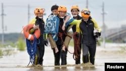 10일 일본 도쿄 북쪽 조소 시에서 수재민이 구조대에 엎혀 침수 지역을 빠져나오고 있다.