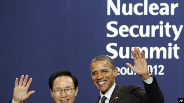 South Korea's President Lee Myung-bak (L) poses with U.S. President Barack Obama as he arrives for a working dinner at the Nuclear Security Summit at the Convention and Exhibition Center in Seoul, March 26, 2012.