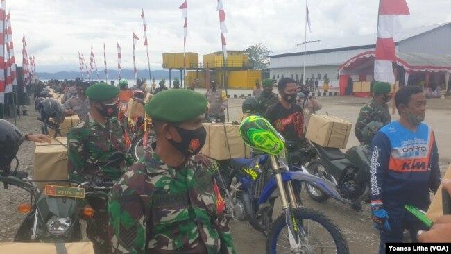 Personel TNI-POLRI menggunakan sepeda motor mendistribusikan bingkisan bantuan sosial untuk masyarakat Poso Pesisir, Kabupaten Poso, Sulawesi Tengah. Rabu (23/12/2020). (Foto: VOA/Yoanes Litha)