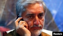 Afghan presidential candidate Abdullah Abdullah talks on his phone during an election campaign after a bomb attack on his convoy in Kabul, June 6, 2014.