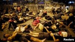 Para demonstran tidur di jalanan untuk memblokade jalan masuk ke kantor pemimpin Hong Kong Leung Chun-ying, Sabtu pagi (5/10).