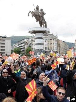 Feligreses ondean bandeas para saludar al papa Francisco a su llegada para celebrar misa en la plaza en Skopie, Macedonia del Norte, el martes, 7 de mayo de 2019.