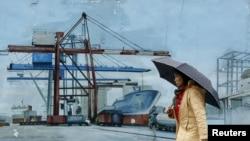 一位女士走過台灣北部基隆港外的一處繪畫。(2016年3月20日資料照)