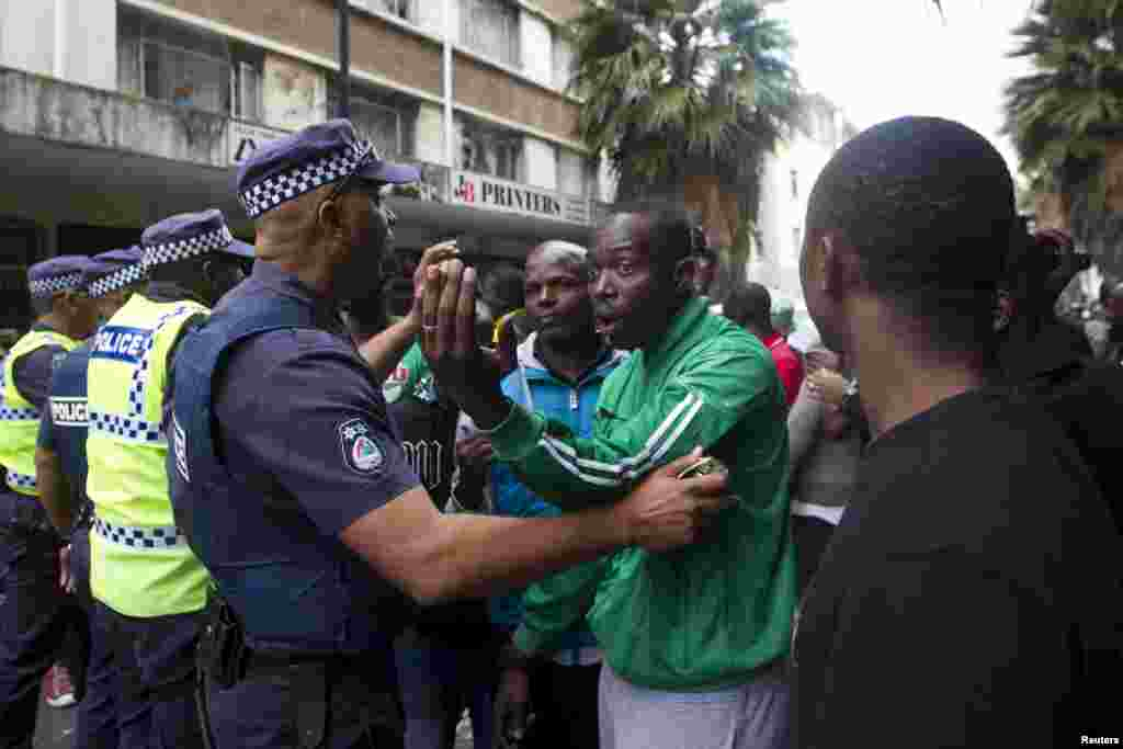 Police encourage a group of foreign nationals to move back to their homes after a peace march in Durban, April 16, 2015.