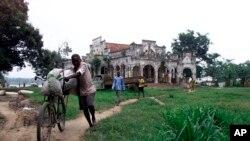 Un homme pousse un vélo à Kisangani, RDC, 1er août 2002.