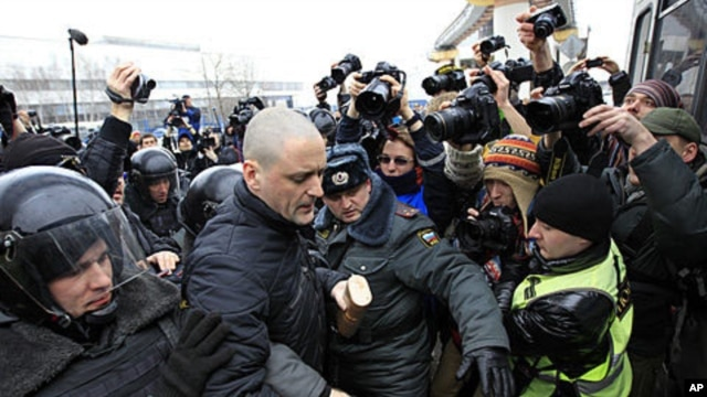 Police officers detain opposition activist Sergei Udaltsov outside the NTV television station in Moscow, Sunday, March, 18, 2012.
