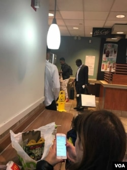 Chatunga Mugabe with a security aide at a McDonald's outlet in New York, USA, carrying Gucci products.
