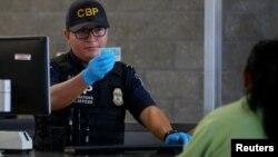 美墨边境移民官员检查入境者文件(资料照片)