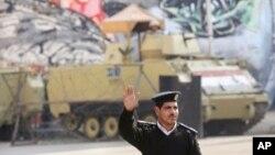 Seorang polisi di depan kendaraan lapis baja di dekat Lapangan Tahrir di Cairo, Mesir, 28/11/2014. Bentrokan di Kairo pada hari Jumat menewaskan setidaknya 3 orang.