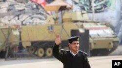 28일 이집트 카이로의 타흐리르 광장에서 경찰 뒤로 장갑차들이 서있다. 이집트 이슬람교도들은 28일 대규모 반정부 시위를 예고하고 있다.