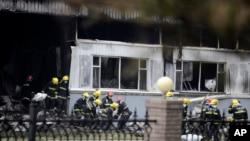 Lính cứu hỏa khiêng thi thể của những nạn nhân bị chết cháy trong vụ hỏa hoạn tại lò mổ gia cầm tại thành phố Ðức Huệ, tỉnh Cát Lâm, ngày 3/6/2013.