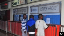 Relatives of passengers on the missing Trigana Air Service flight stand in front of its closed offices at Sentani airport in Jayapura, Papua province, Indonesia, Aug. 16, 2015.