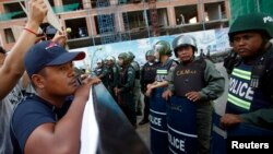 Police officers block a street as protesters demand the release of five opposition members of parliament, near the Phnom Penh Municipal Court in central Phnom Penh, July 16, 2014.
