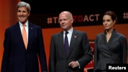 From left, U.S. Secretary of State John Kerry, Britain's Foreign Secretary William Hague and actress and campaigner Angelina Jolie gather at a summit to end sexual violence in conflict in London, June 13, 2014.