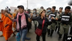 FILE - Cambodian civil rights supporters are forcibly directed by riot police as they march in protest of charges brought against local rights activists near Prey Sar prison, outside Phnom Penh, Cambodia, May 9, 2016.