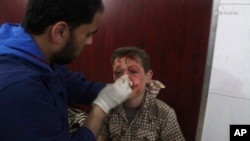 This photo provided by the Syrian anti-government activist group Ghouta Media Center, which has been authenticated based on its contents and other AP reporting, shows a Syrian doctor treating a boy who was wounded by Syrian government forces shelling, at a makeshift hospital in the Hamouriyya neighborhood, an eastern suburb of Damascus, Syria, May 16, 2017.