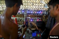 FILE - Rohingya Muslims charge their phone batteries in a shop at a refugee camp outside Sittwe, Myanmar, May 21, 2015.