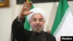 Zababben Shugaban Iran Hassan Rohani yana daga manema labarai hannu a ganawa da yi da su a birnin Tehran ran 17 ga watan Yunin 2013.