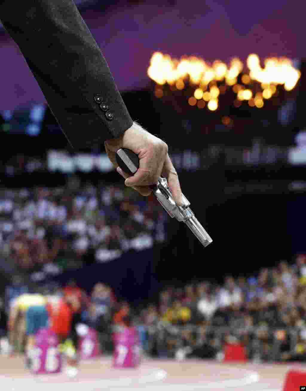 Un oficial sostiene la pistola de salida en los 400 metros.