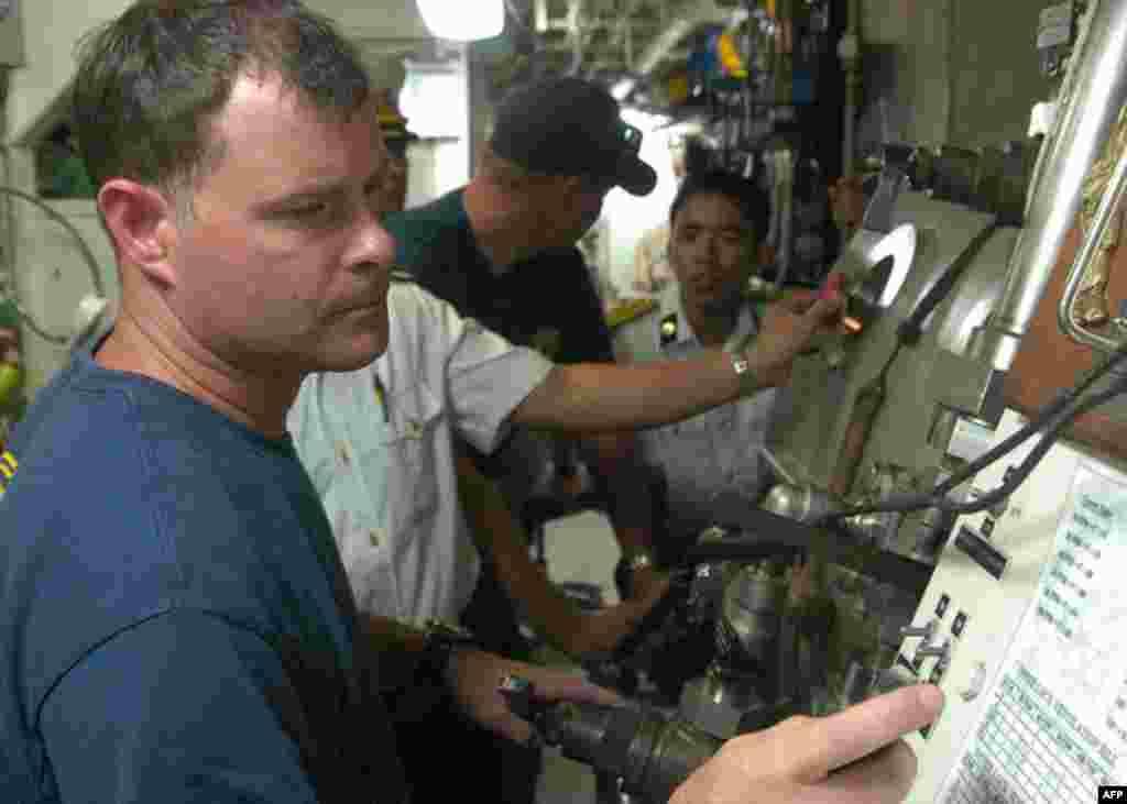 Đội trưởng nhóm thợ lặn của hải quân Hoa Kỳ Brian Wilcox định giờ 1 đợt lặn giả tưởng tại phòng nén khí trên tàu USNS Safeguard trong khuôn khổ diễn ra Hoạt động Giao lưu Hải quân (NEA) với Việt Nam. (Bản quyền của Hải quân Hoa Kỳ, ảnh do Hạ sĩ kiêm Chuyê